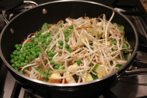 adding sprouts and peas